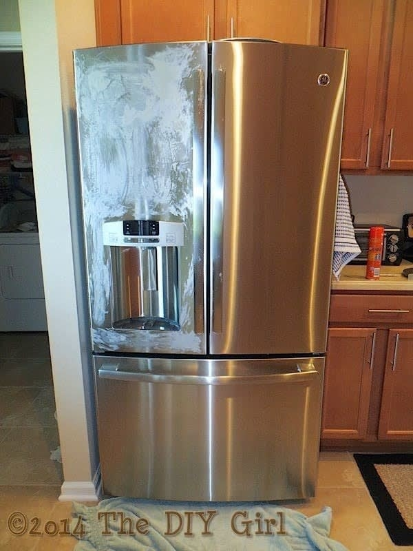 The blogger's stainless fridge, a towel laid down in front of it, one door covered in dried Pledge