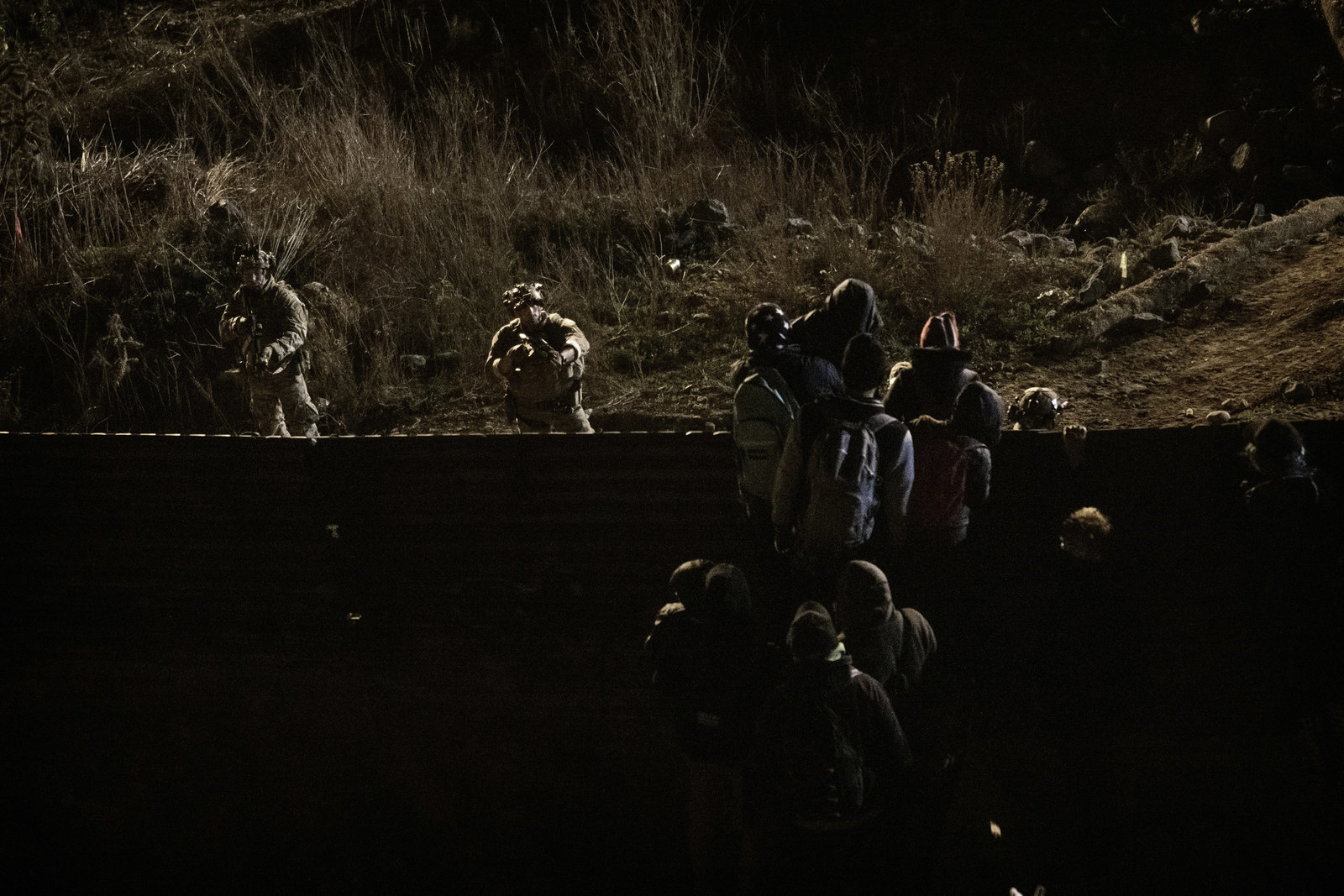 U.S. Border Protection officers point their weapons at migrants as they prepare to cross the border fence to get into the U.S. side to San Diego.