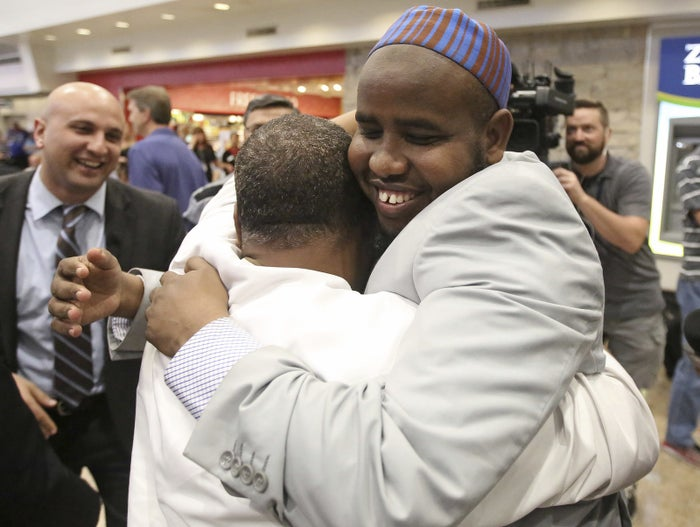 Imam Yussuf Abdi, right, hugs a friend after arriving at Salt Lake City International Airport in June 2017.