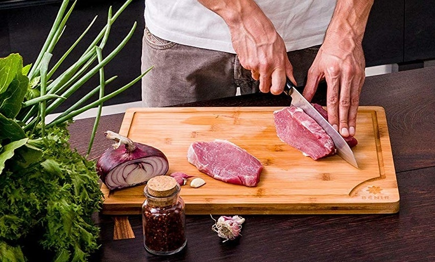 person cutting up a slab of steak on the cutting board