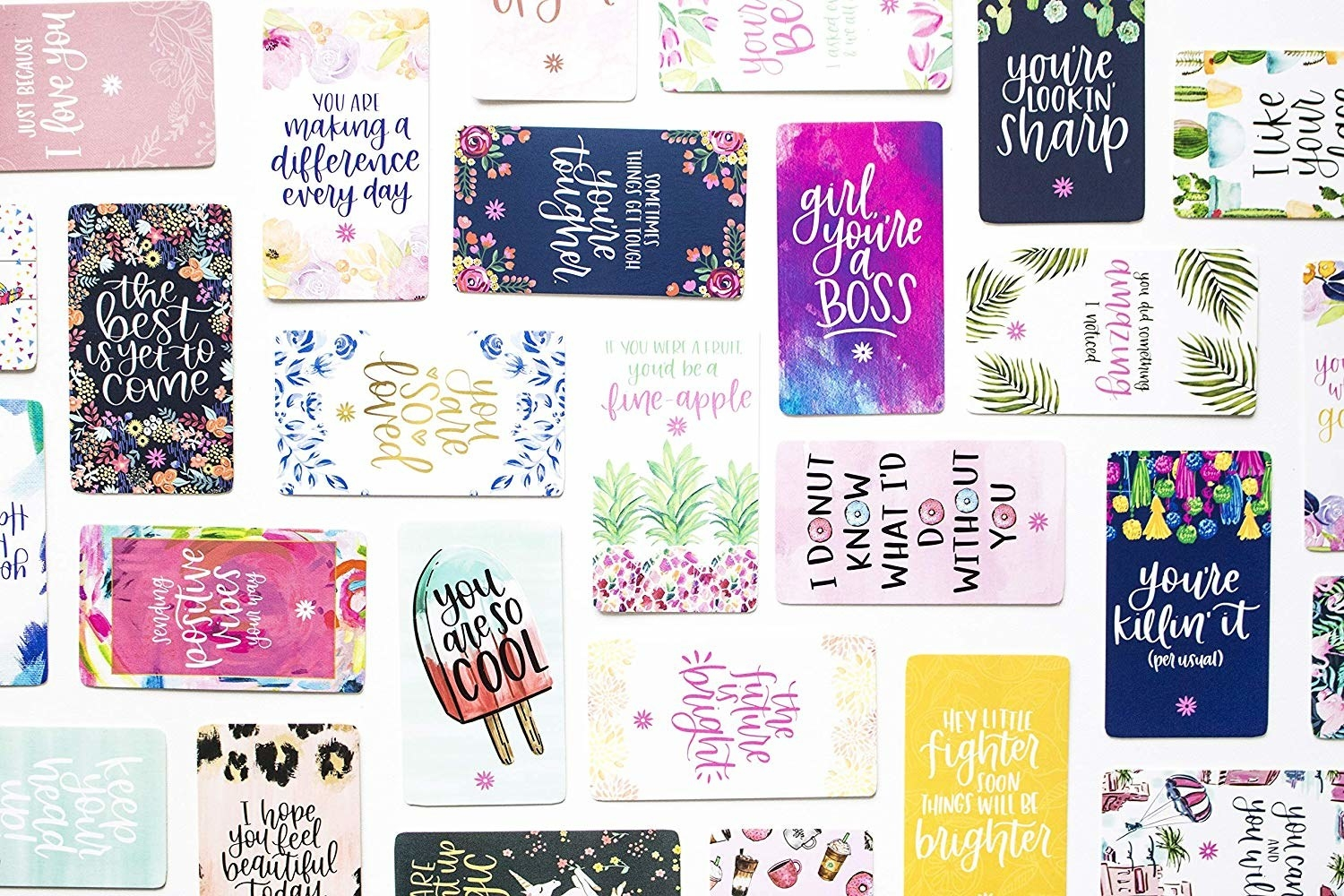 different cards with illustrations and kind messages laid out