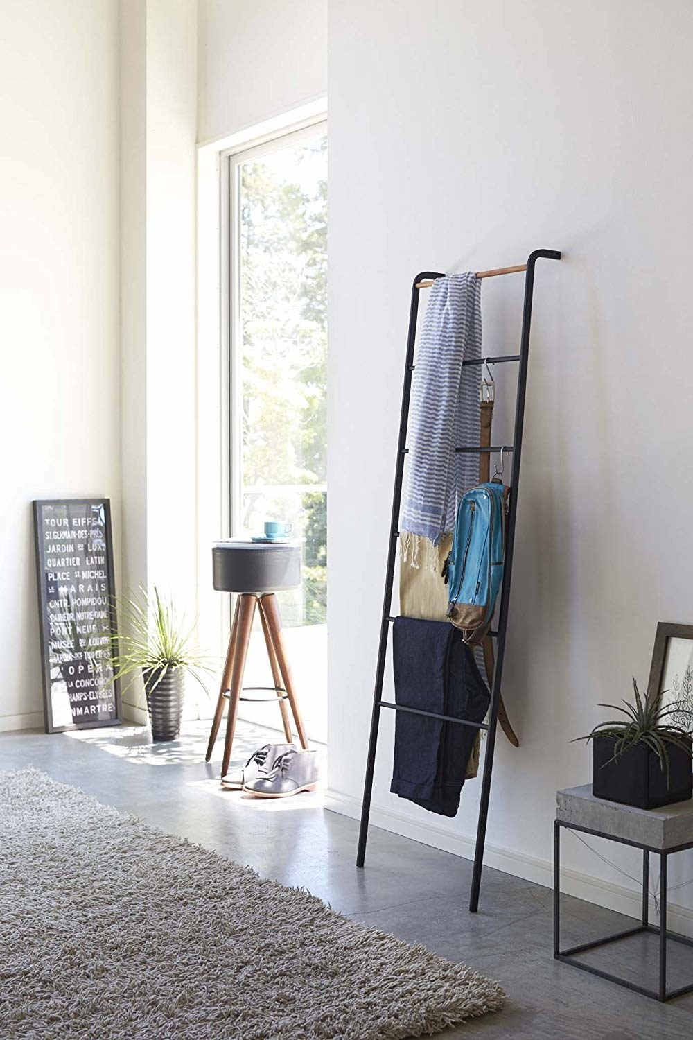 Black pipe and natural wood leaning ladder with clothes hanging on rungs