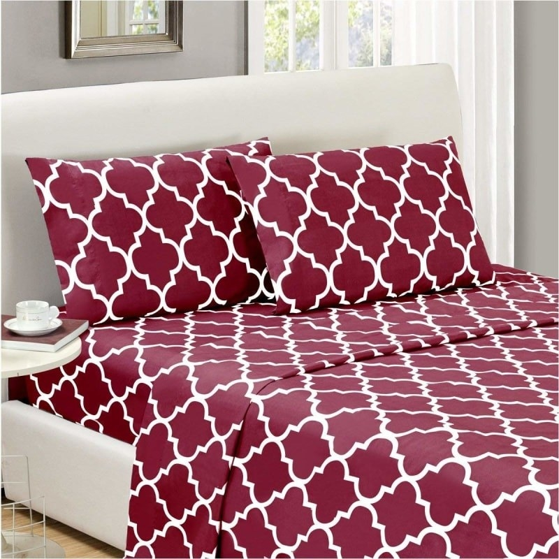 Red sheets and pillowcases with a white Quatrefoil design on a bed