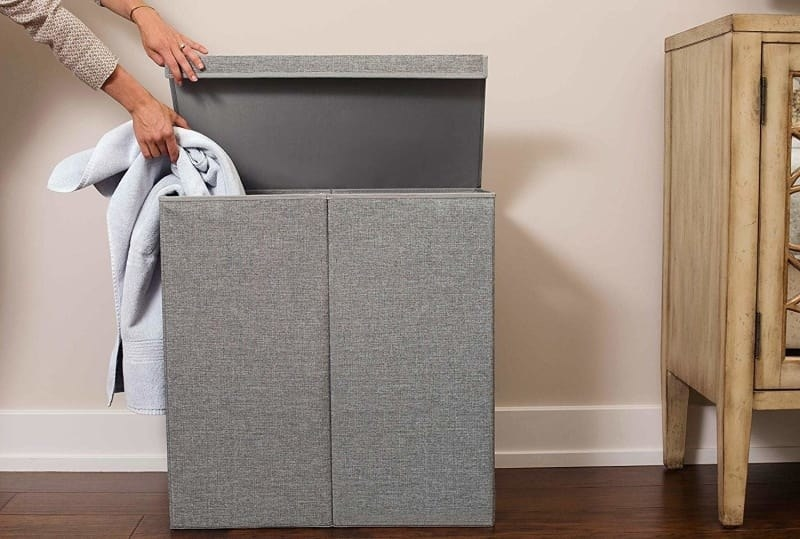 The laundry basket in grey with a model lifting the attached lid to put a towel into one of the two compartments