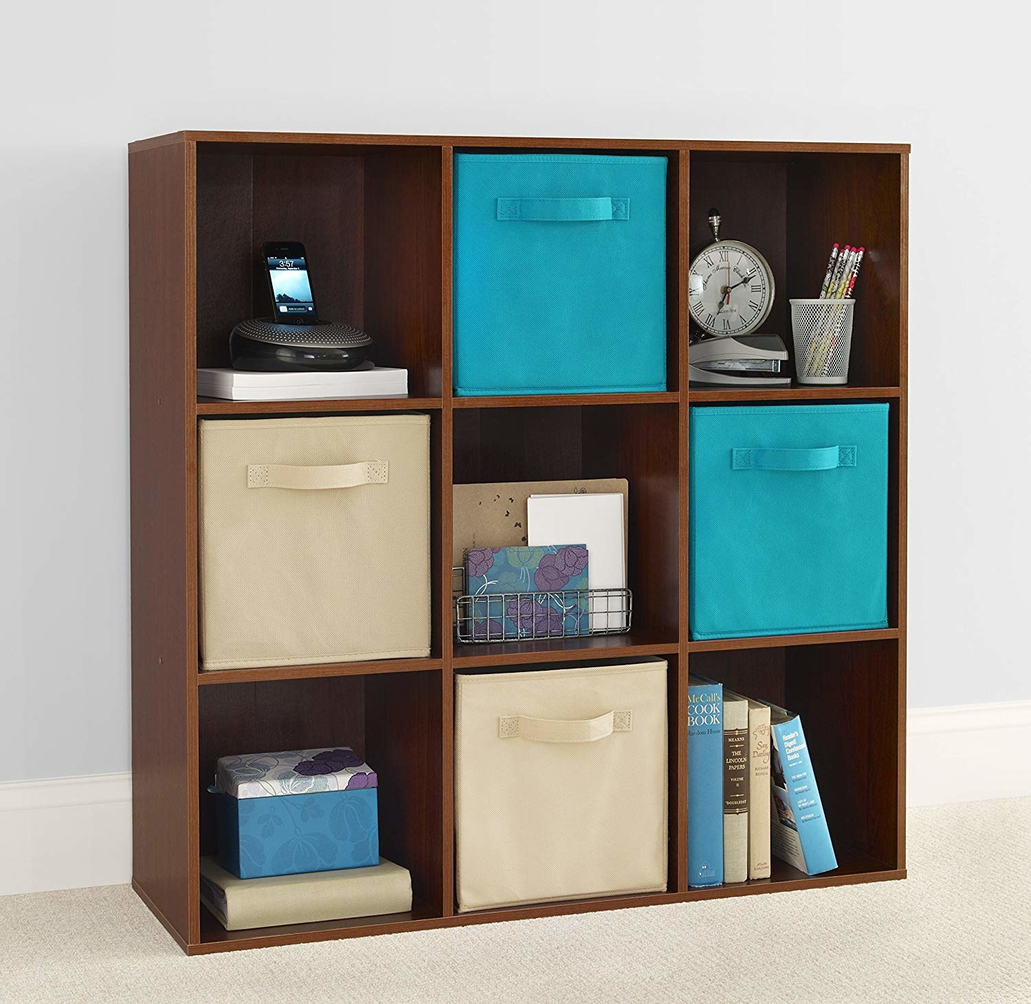 brown nine-cube organizer with four fabric drawers and other random stuff in each cube