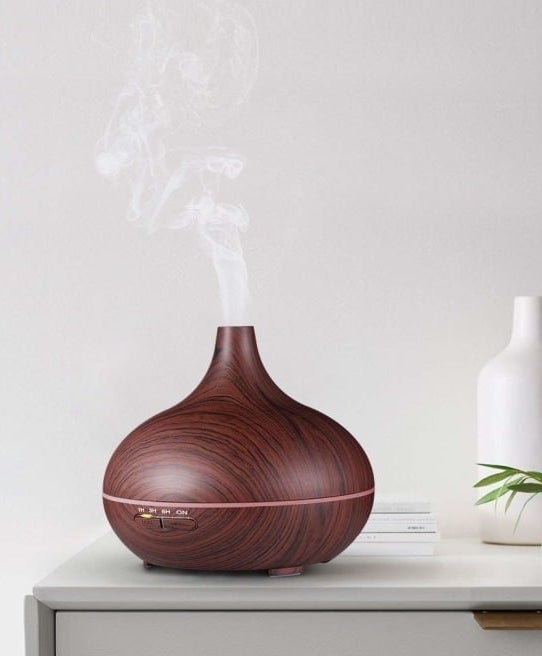The diffuser in brown with a wood-like pattern sitting on a table releasing steam into the air