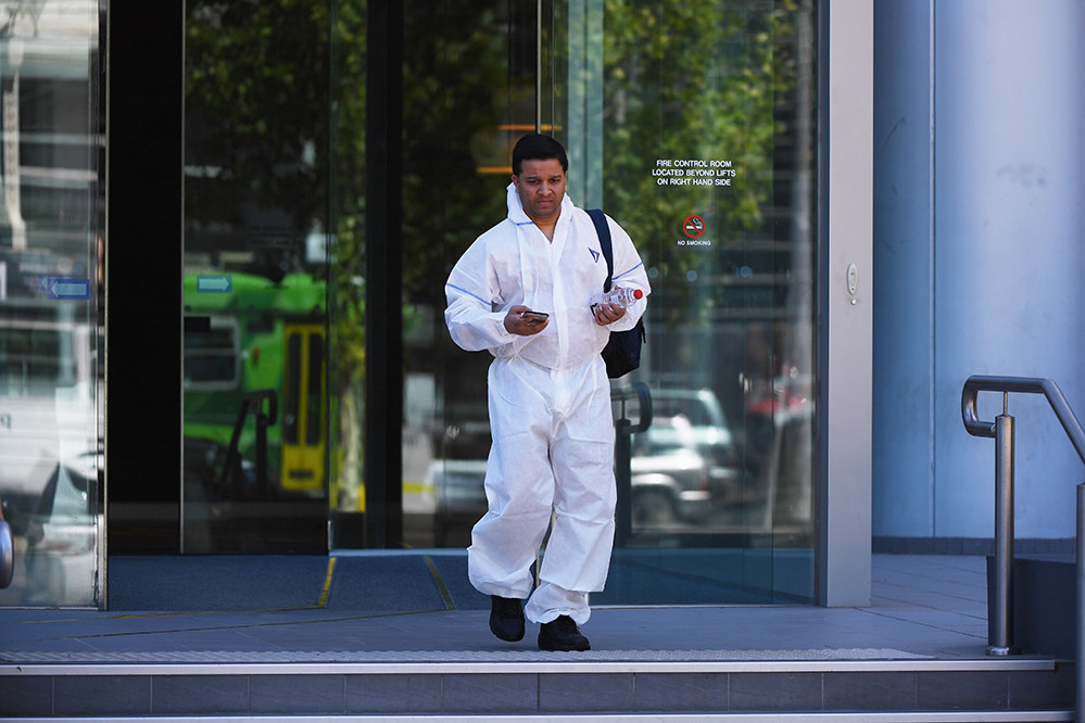 An emergency services worker in a hazmat suit leaves the South Korean consulate building in Melbourne
