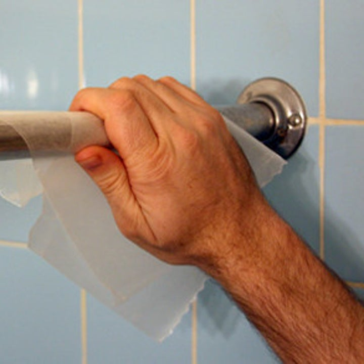 hand using wax paper on curtain rod