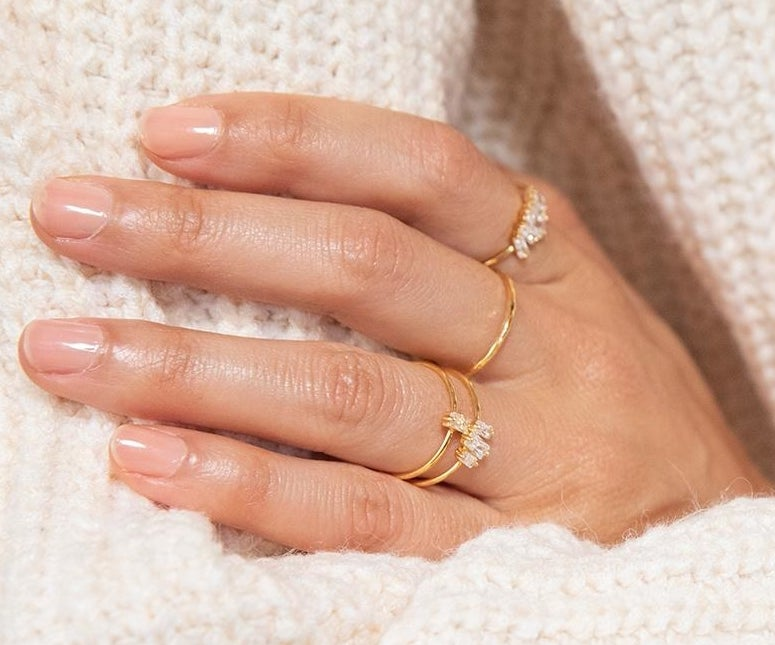 a hand wearing the dainty gold rings