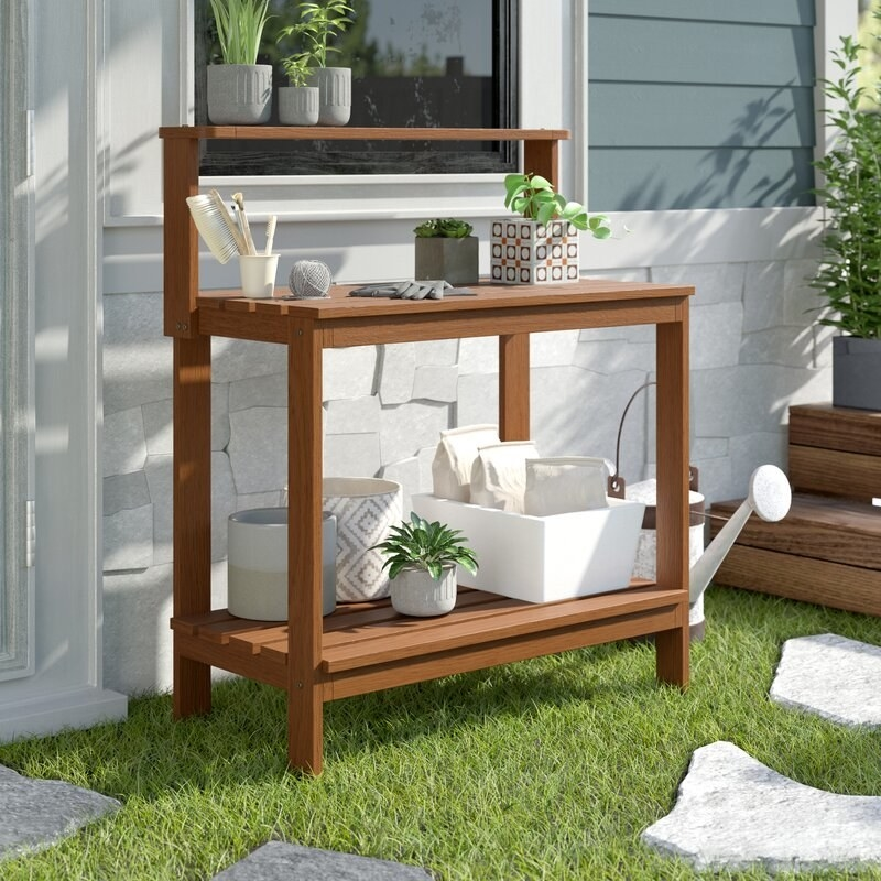 """Promising review: """"This is a very sturdy little potting bench. My plants are arranged on all the shelves, and I like the spaces between the boards for water to drain out. I can move the bench easily if I want to rearrange my outdoor furniture. It is perfect. Thanks!"""" —MorganPrice: $108.99 (originally $249.99)"""