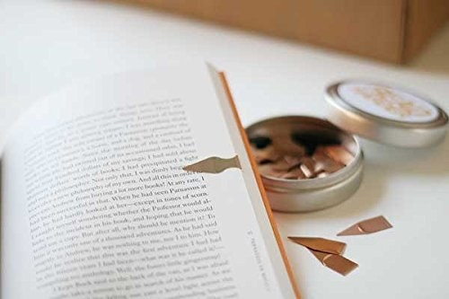 the book markers in a tin with one on a book