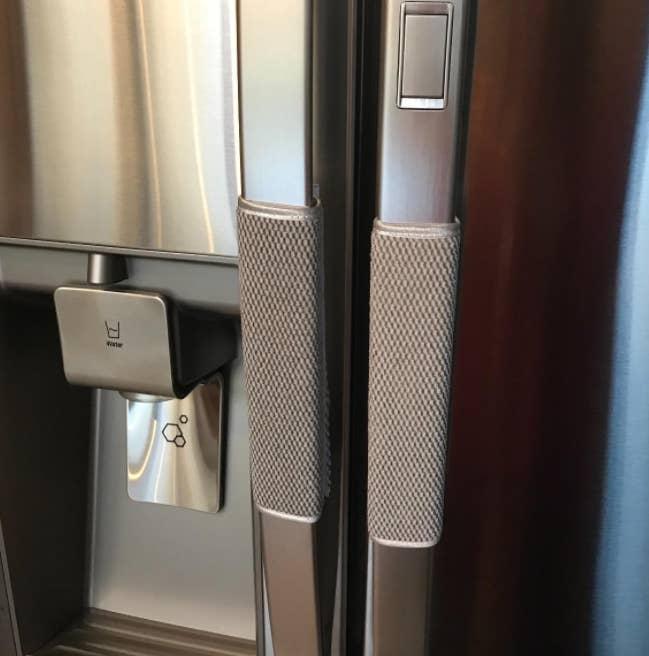 gray clothes on fridge door handles