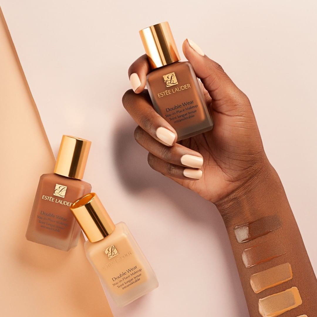 model hand holding bottle with different colors swatched on arm