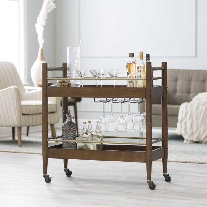 """Promising review: """"Bar cart prices can be pretty steep and this one was reasonably priced, so I wasn't sure if the quality was where they cut corners. That was not the case. I'm really happy with what I received. It's sturdy, looks great, and does not look cheap. The size is perfect for us. It's not too bulky, but it's large enough to hold drinks, glasses, snacks, etc. We don't really move this around, but it moves without a problem and the lock feature holds it in place. My husband assembled it and he had no problem with it. If you're looking for wooden bar cart that's sturdy and has clean design, I recommend this product."""" —M YooPrice: $163.18"""