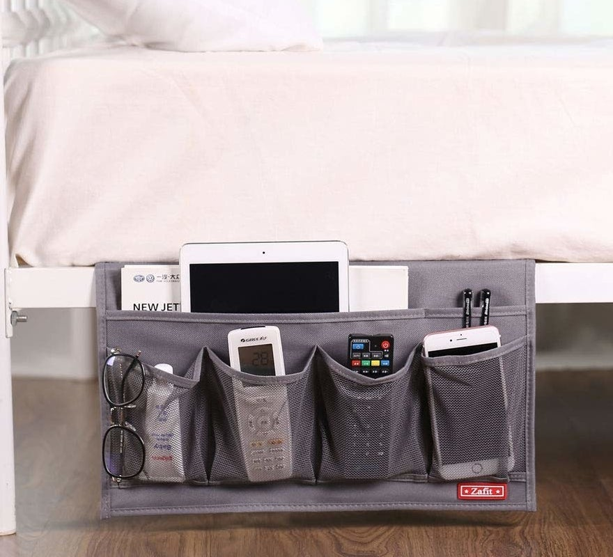 """This organizer is designed with six pockets, meaning you can store everything from an iPad and cell phone to glasses and hand cream. Promising review: """"This is very helpful if you have a lot of small items on your bed. I use this to store my iPhone battery case, cables, flash drives, etc."""" —NickGet it from Amazon for $11.99."""
