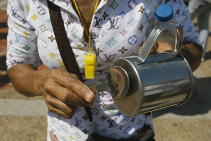 A woman bangs a metal cup during an opposition demonstration in La Guaira, Feb. 2, 2019.