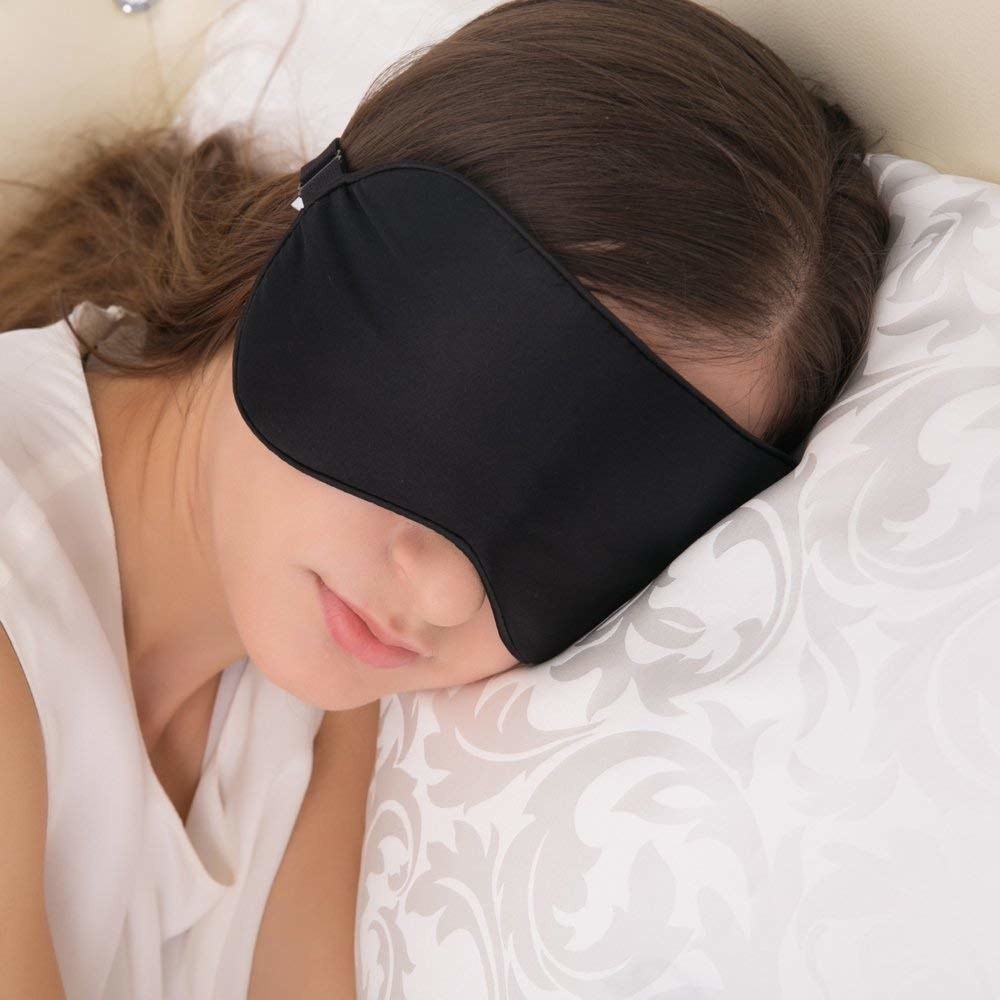 A person wearing the eye mask as they sleep