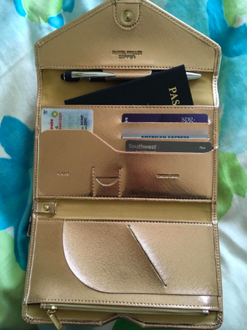 reviewer image of the wallet open showing different pockets for cards, passport, documents
