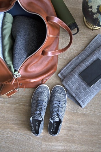 pair of gray sneakers sitting next to travel bag