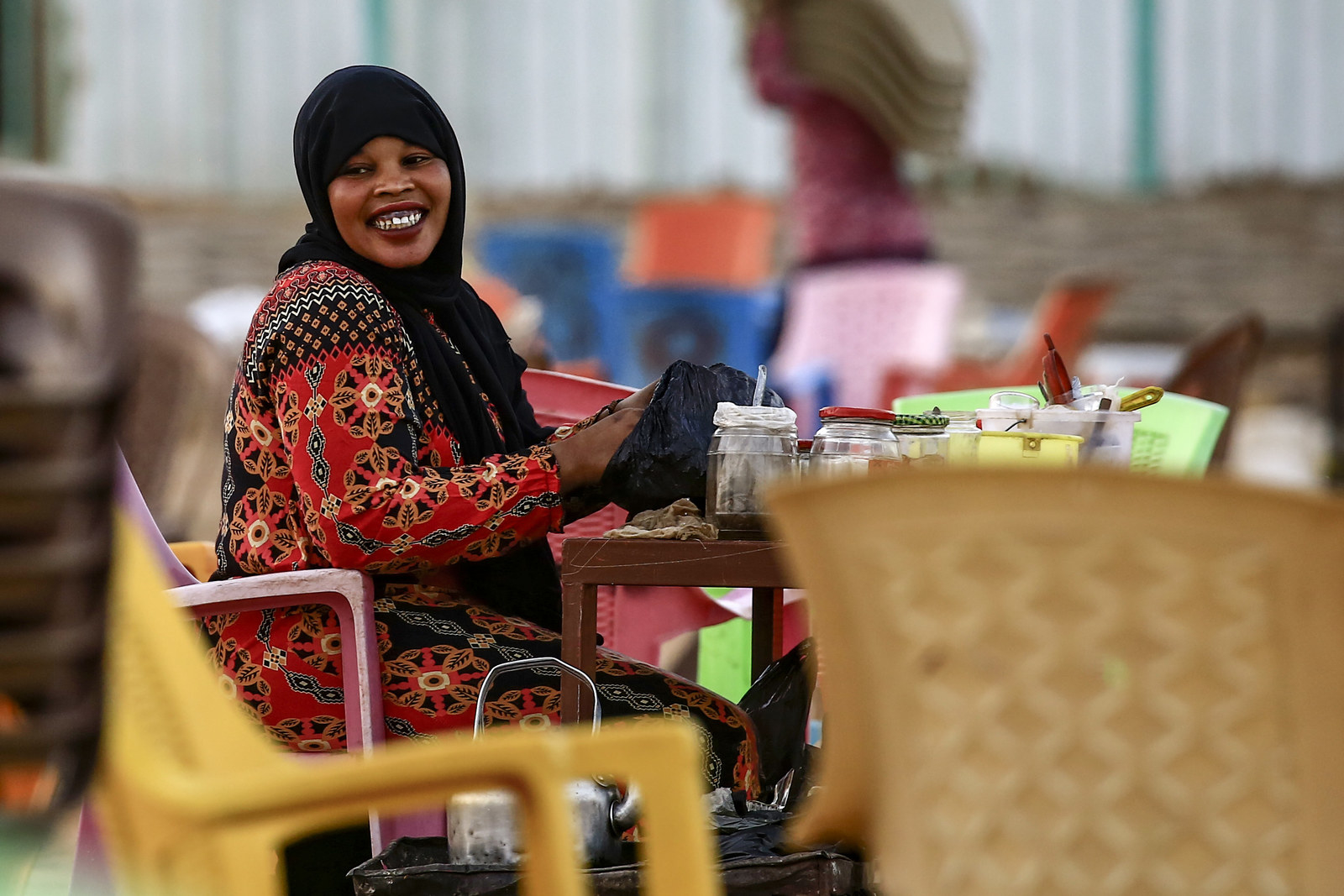 A Sudanese woman prepares tea as she sits at her spot along the capital Khartoum's Nile Street on February 10, 2019. - Tea-sellers had been earlier banned for months from the popular Nile Street.