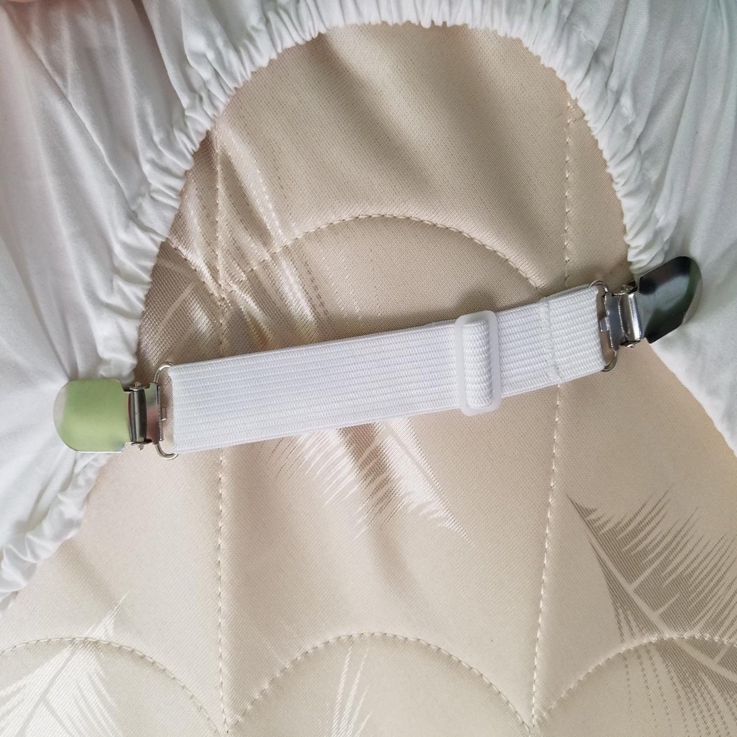 The elastic fastener features two metal clips on each side to grip the fitted sheet