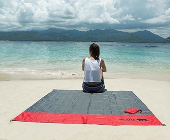 blanket spread out at beach and person sitting on it