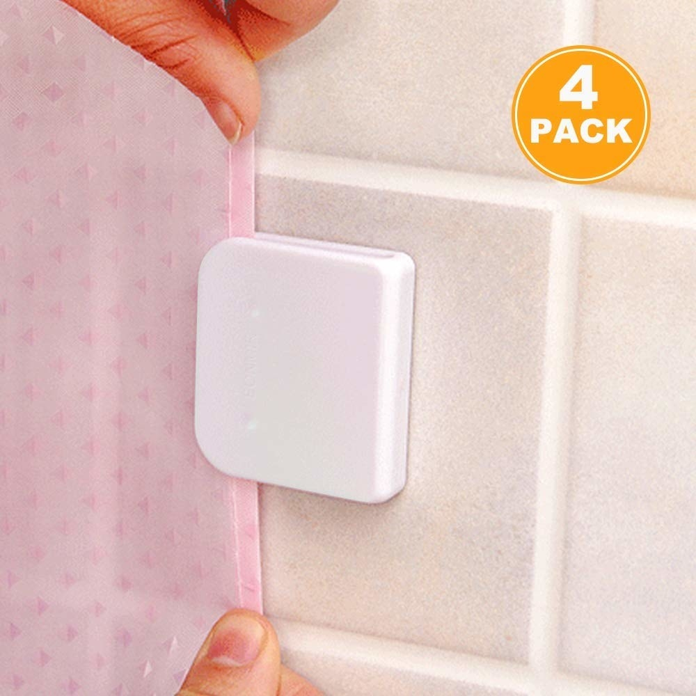 a white shower clip attached to a wall holding a curtain in place