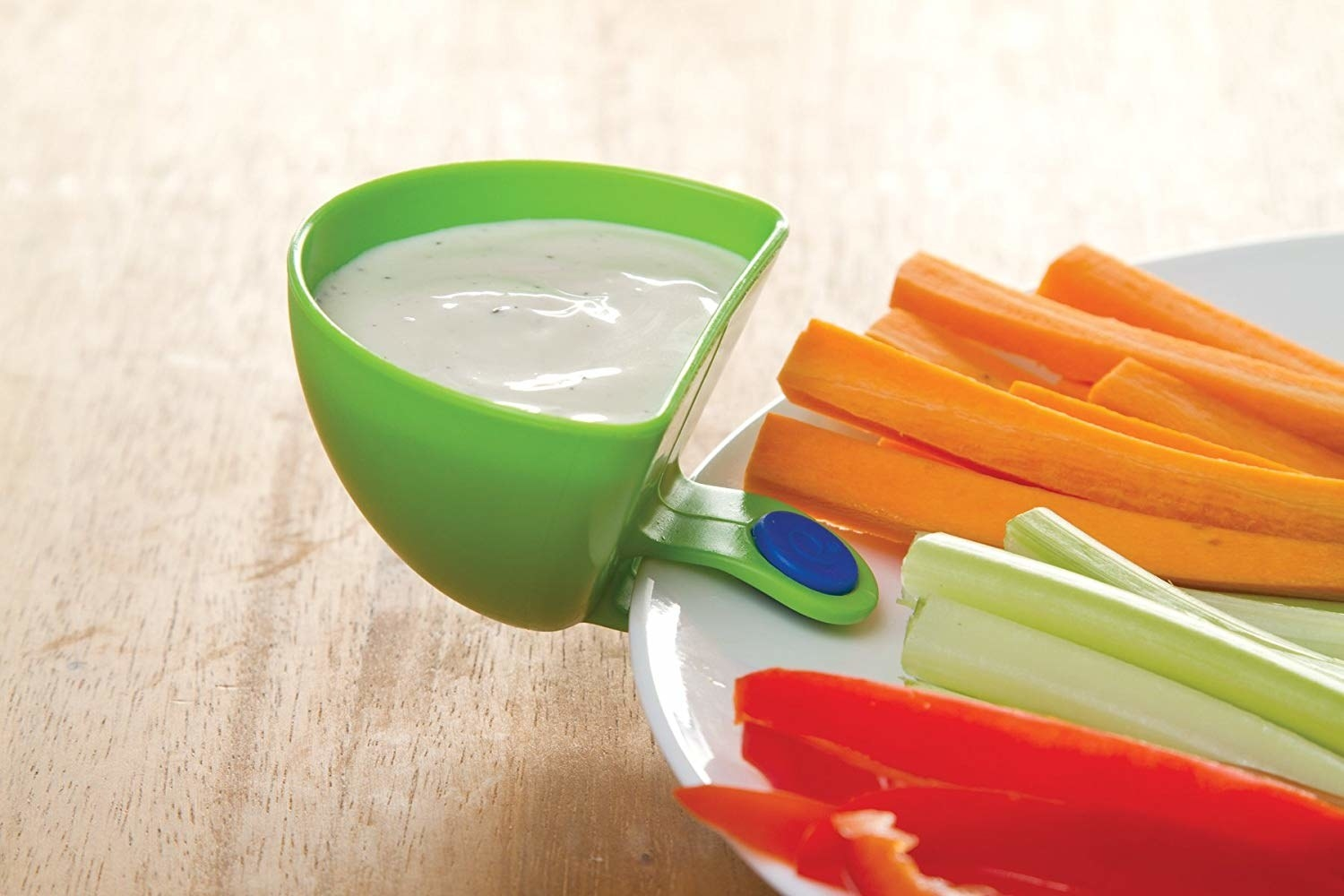 dip clip filled with ranch dressing and securtely attached to a dinner plat that has strips of veggies for snacking