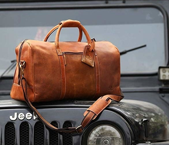 the leather weekender bag sitting on top of a Jeep