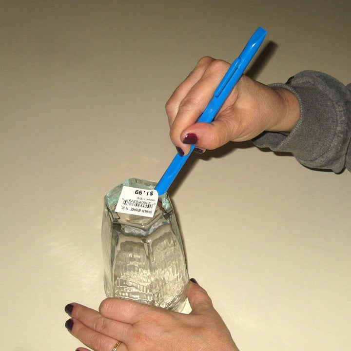 a pair of hands using the scratch-free scraper tool to remove a label from some glassware