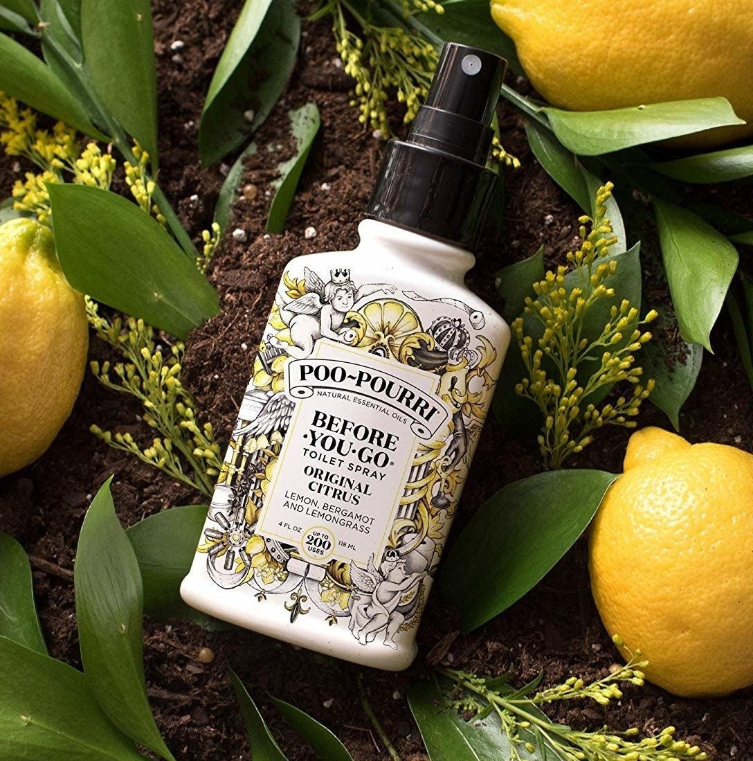 the bottle of poo-pourri photographed outside near plants and lemons