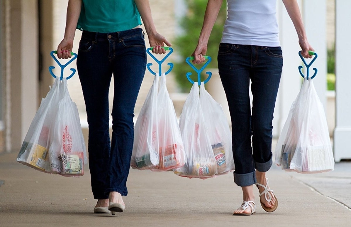 two models walking with grocery bags in each hand held by the bag carriers