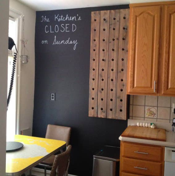 """A kitchen wall painted with the chalkboard paint, with the words """"The Kitchen's CLOSED on Sunday"""" written in chalk"""