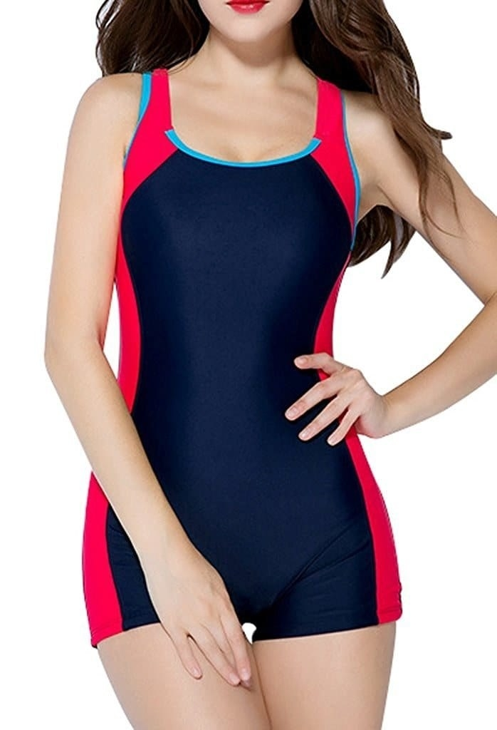 model wearing the tank-top style one piece with shorts in navy blue with red stripes down the sides