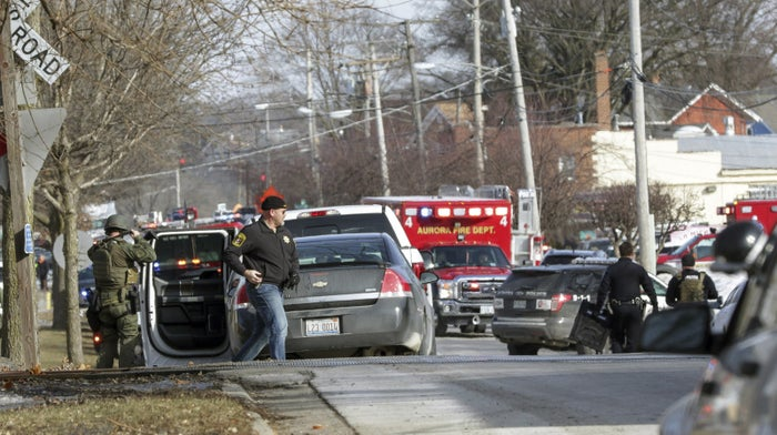 Law enforcement personnel gather near the scene of the shooting in Aurora, Illinois.