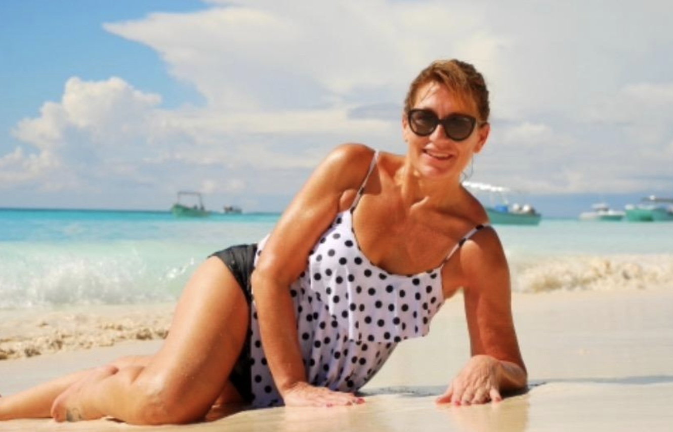 reviewer wearing the bathing suit with black short bottoms and a ruffle tank top in white with black polka dots
