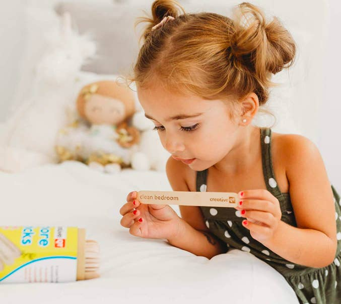 """Child holding up large popsicle stick that says """"clean bedroom"""""""