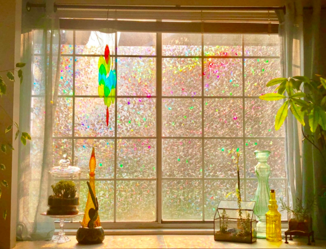 a reviewer's photo of the privacy window film with colorful light streaming through a large window