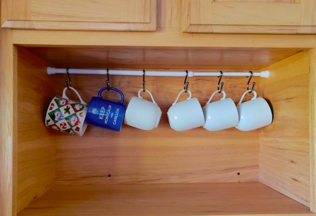 Reviewer image of tension rod in a cabinet holding up mugs with S-hooks