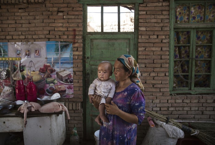 A Uighur woman holds a child in her home in Xinjiang.