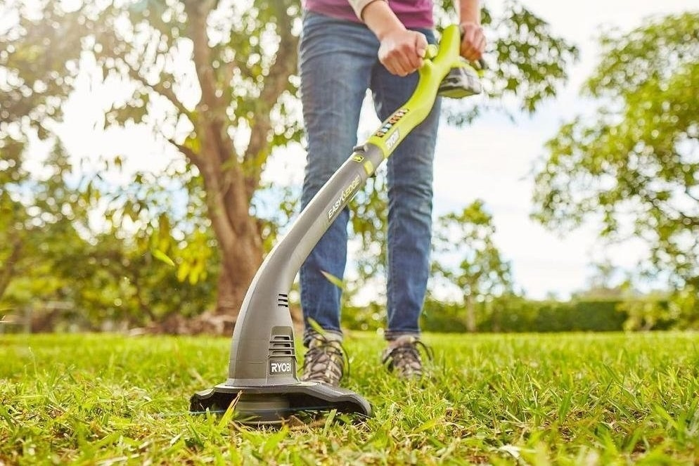 a person using the weed whacker