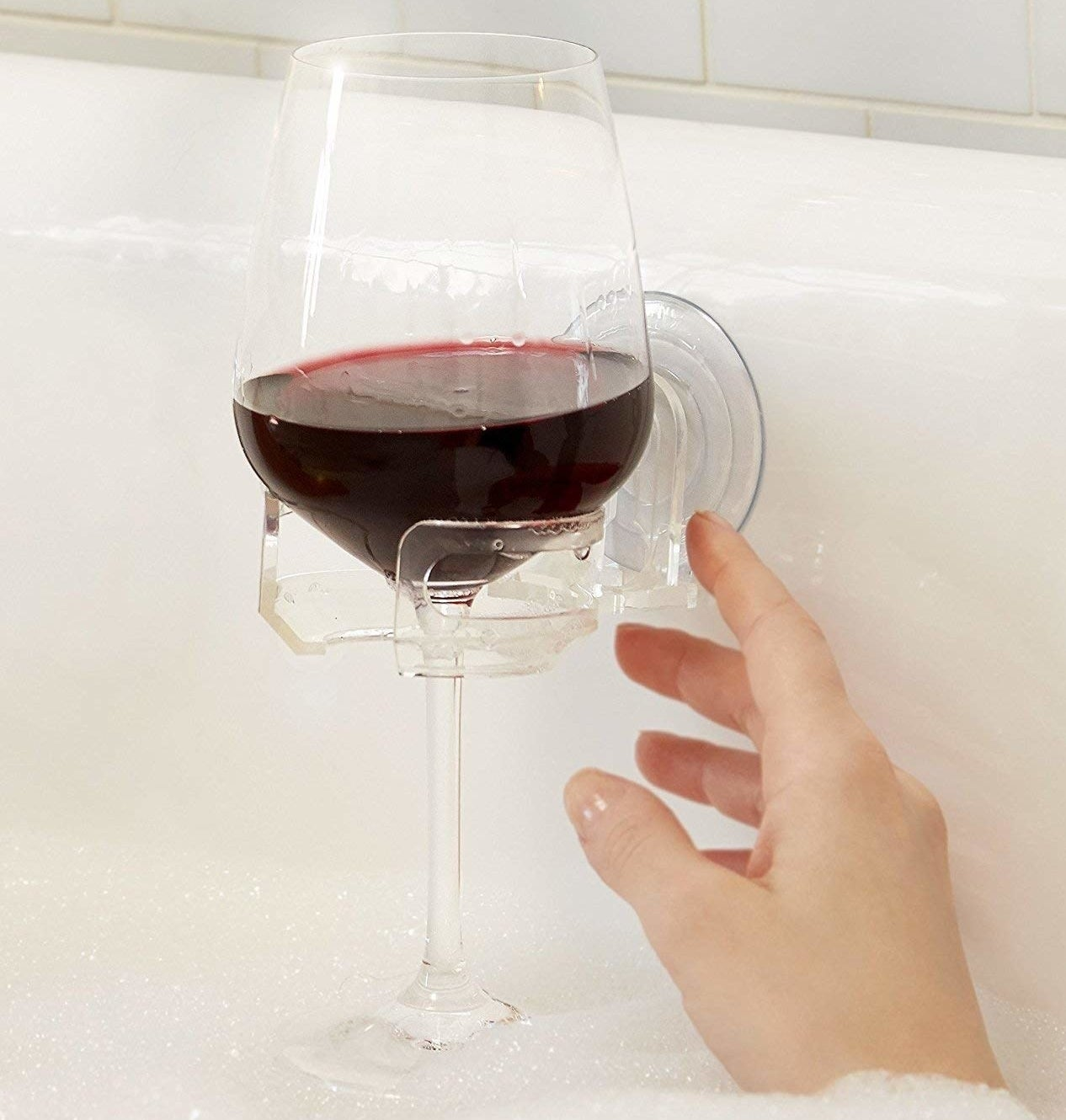 person using the glass holder in the bath