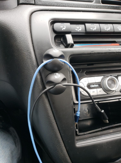 Two cable clips attached to the dashboard of a car holding two charging cords off the ground