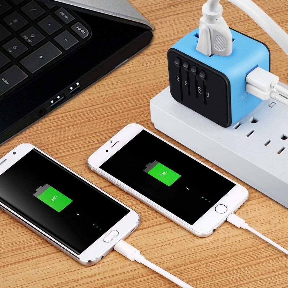 two phones plugged into a blue travel adapter