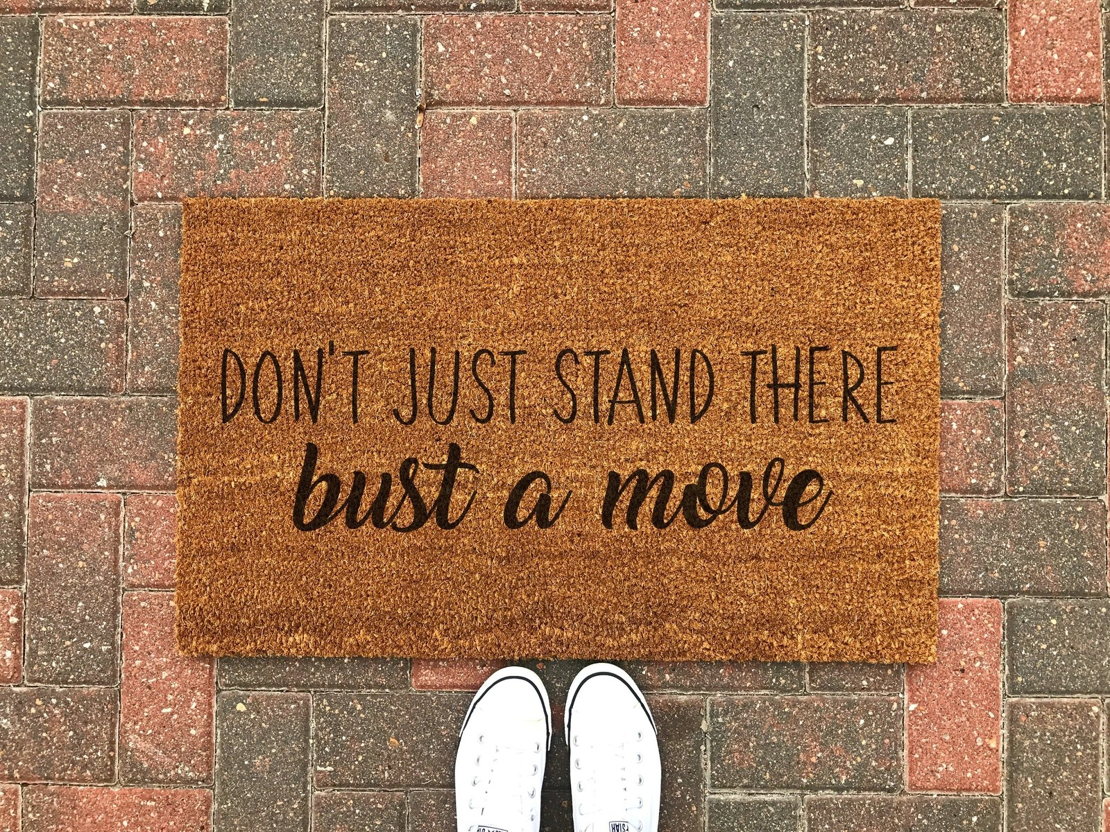 """beige coir doormat with black text that says """"don't just stand there, bust a move"""""""