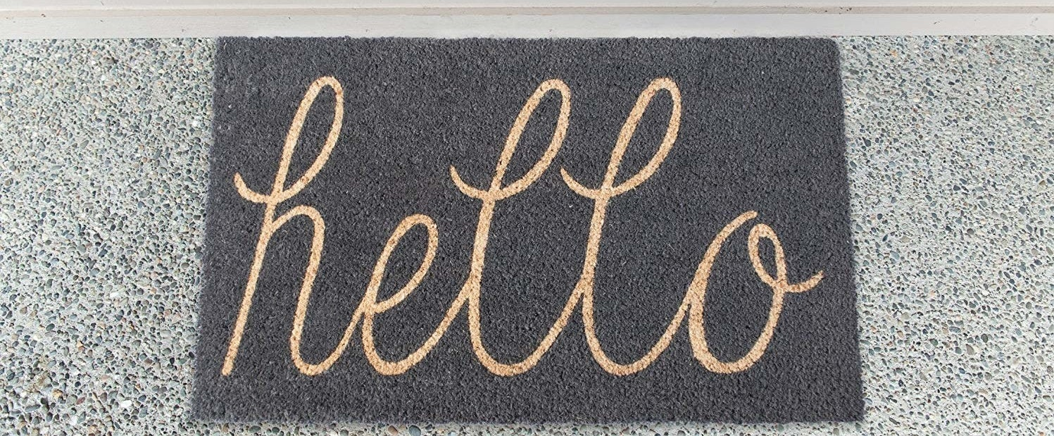 the black mat with gold script writing that reads hello