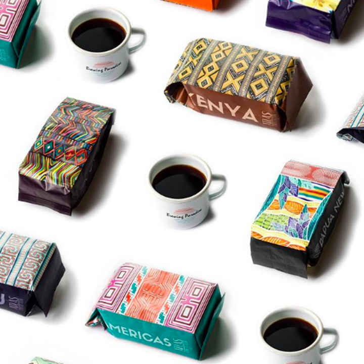 An organized flat-lay of mugs of coffee and colorful bags of coffee beans