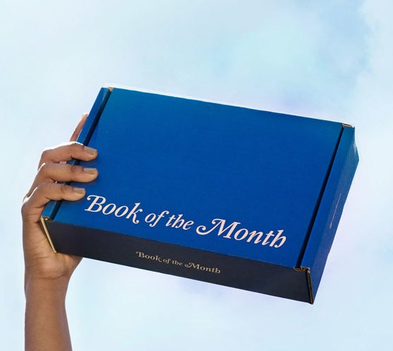 Hand holding book of the month box.