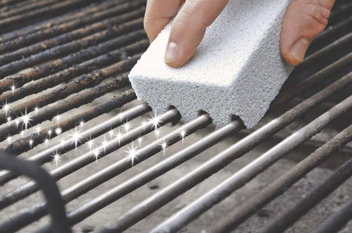 A sponge-like cleaner picking up grime on a dirty grill