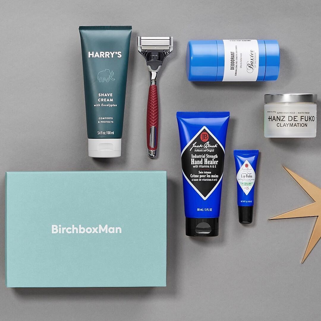 "A  ""Birchbox Man"" box flatlay with Harry's shaving cream and a razor, deodorant, hair cream, Jack Black hand cream, and lip balm"